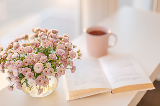 small pink flowers bouquet in glass vase with blurred soft focused book and pink cup of tea
