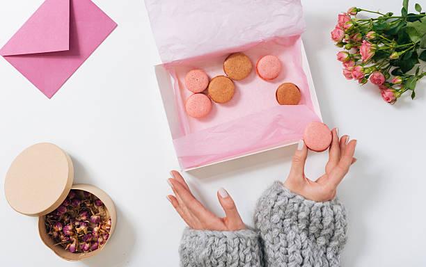 small pink macaroon being in hands of a woman - rosentorte stock-fotos und bilder