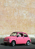 Tiny pink vintage car in Rome, Italy