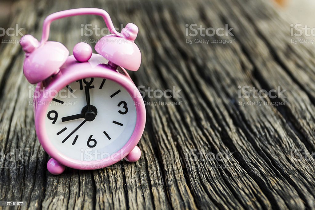 Small pink watch on wood. royalty-free stock photo