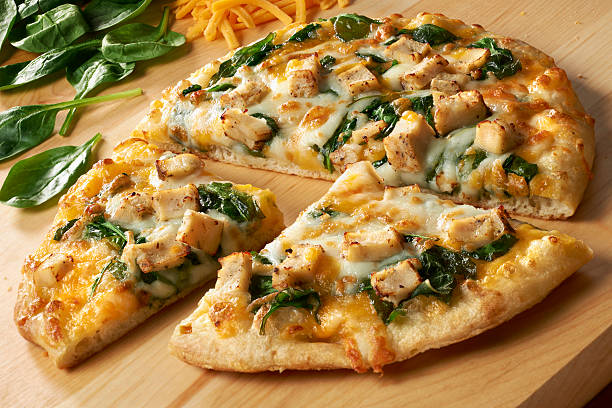 """Small Pizza with Chicken, Spinach and double cheese """"Small personal sized pizza with white meat chicken, spinach, cheddar and mozerella cheese. On a wood cutting board with ingredients around.See more Pizza shots in my Pizza/Snacks/Sandwich Lightbox."""" burwellphotography stock pictures, royalty-free photos & images"""