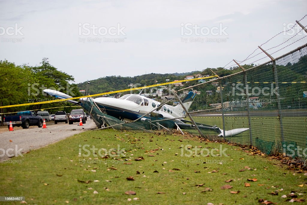 small plane crashes through fence on highway in emergency landing stock photo