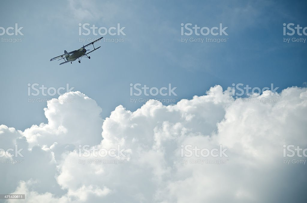 Small plane flying above the clouds in the blue sky stock photo
