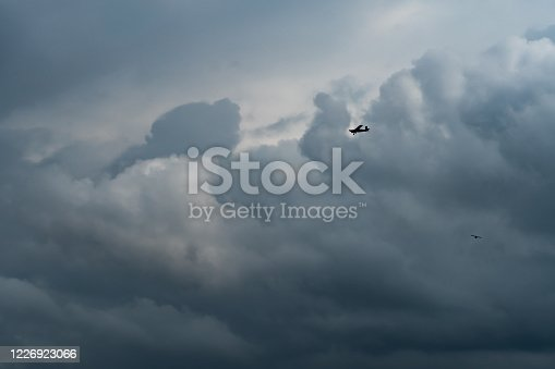 Small plane in cloudy sky for rainmaking. White fluffy clouds with small aircraft to make artificial rainfall. Two airplane flying on cloudy sky. Agricultural airplane for artificial precipitation.