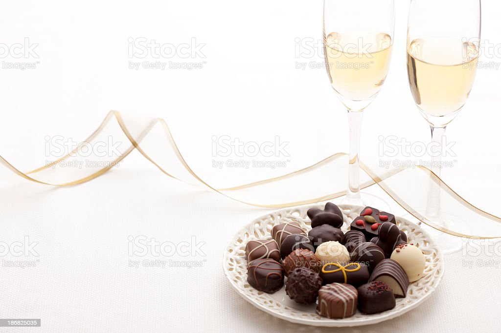 Small plate with chocolate and two glasses with champagne royalty-free stock photo