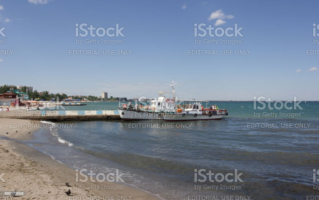 A small pleasure boat at the pier. Small waves rolled on the sandy shore stock photo