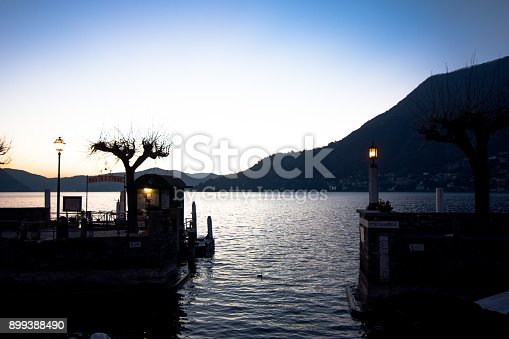 Small port of a town on Lake Como with storage of fishing boats and berth for ferries for public transport on the lake. Lights at sunset from the port of the village of Torno on Como Lake