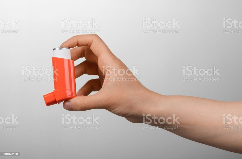 Small portable inhaler in female hand on gray stock photo