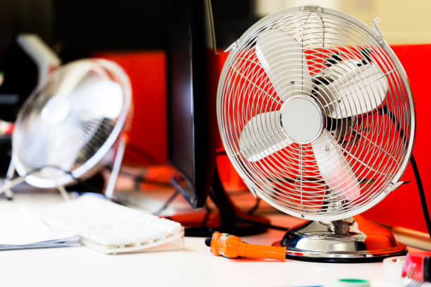 Small, portable switched off fan on desk in office stock photo