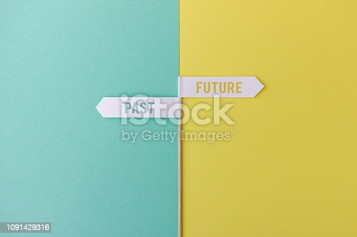 Wood stick with small white flags on yellow and blue background showing past and future