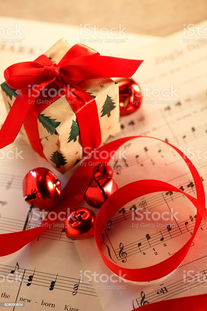 Small Present Resting On Christmas Sheet Music stock photo