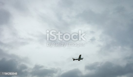 Small private plane flying in cloudy sky. White crop duster flight in stormy sky