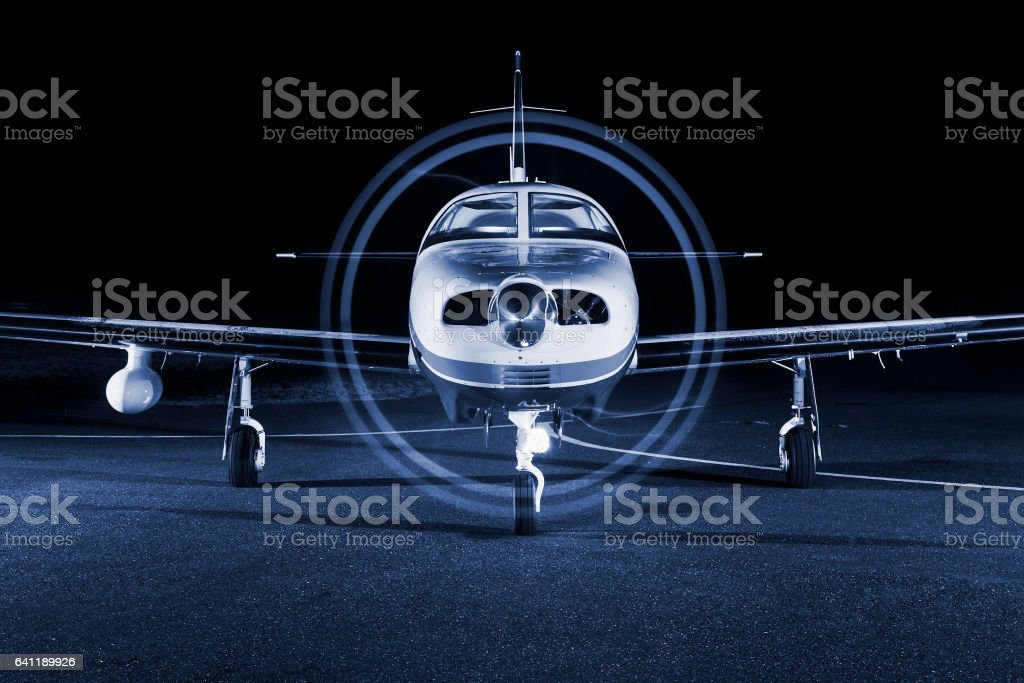 Small private single-engine piston aircraft on runway, front view, night photo stock photo