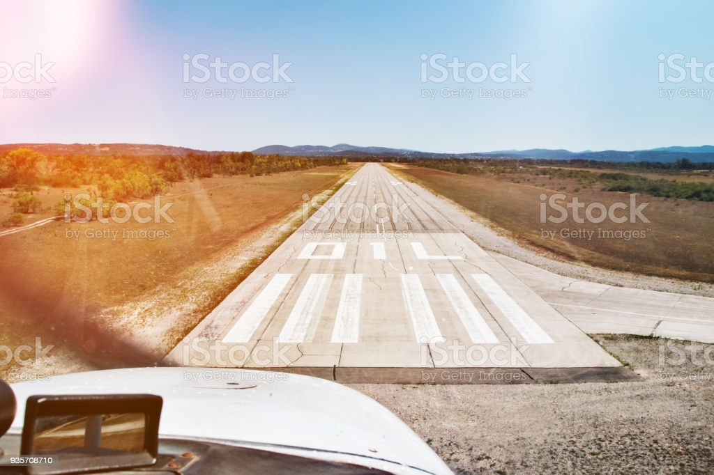 Small propeller airplane landing on rural airport runway view from cockpit interior stock photo