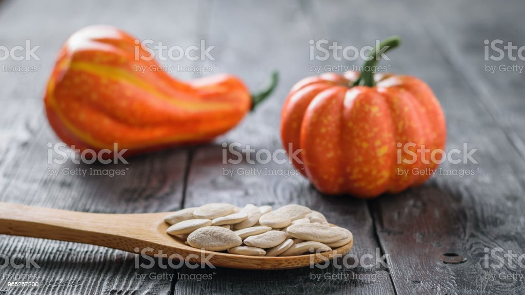 A small pumpkin of unusual shape and a spoon with pumpkin seeds on a wooden rustic table. zbiór zdjęć royalty-free