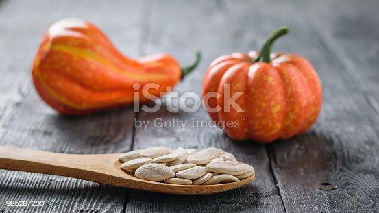 A Small Pumpkin Of Unusual Shape And A Spoon With Pumpkin Seeds On A Wooden Rustic Table - Stockowe zdjęcia i więcej obrazów Bez ludzi