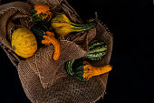 small pumpkins for decoration in a basket lined with flax