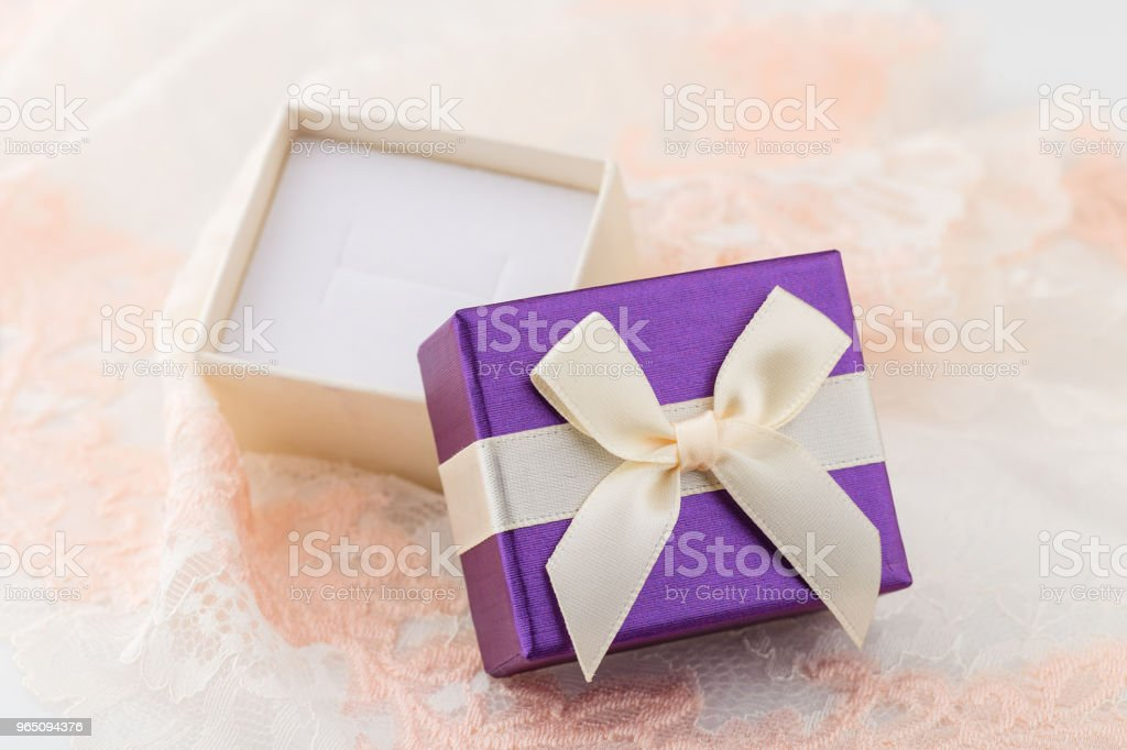 Small purple jewelry gift box with bow on lace background royalty-free stock photo