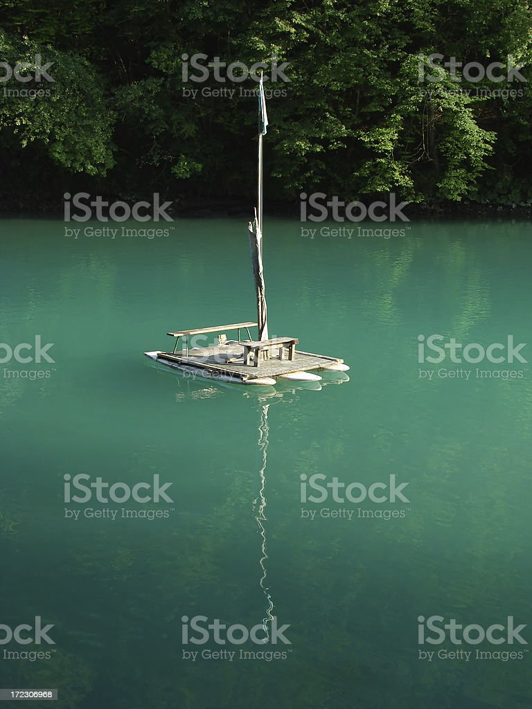 small raft on silent turquoise blue water surface stock photo