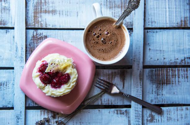 eine kleine himbeer kuchen und eine heiße schokolade becher. - heiße schokoladen cupcakes stock-fotos und bilder