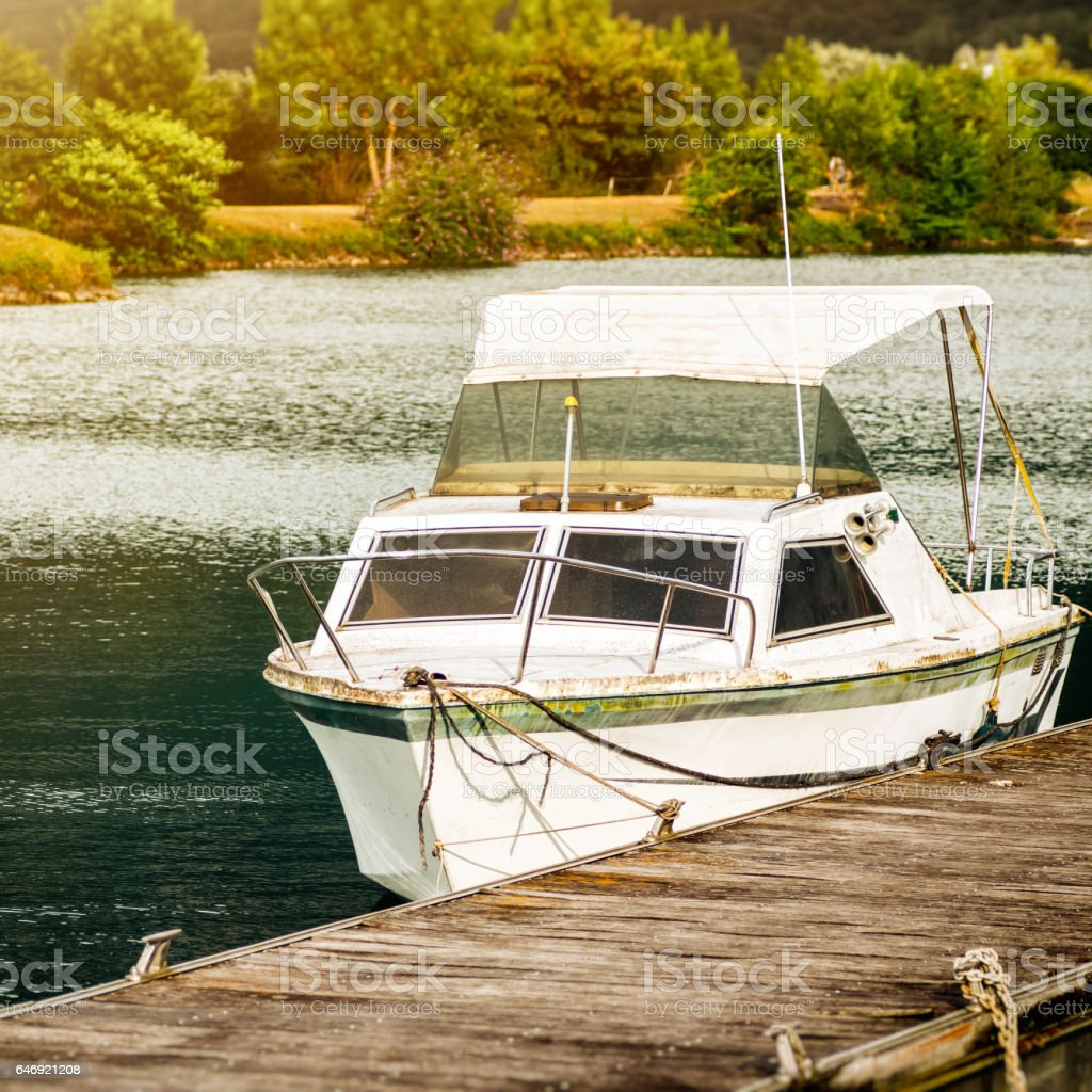 Small recreational white color boat at deck on wooden pier in harbor marina bay in France stock photo