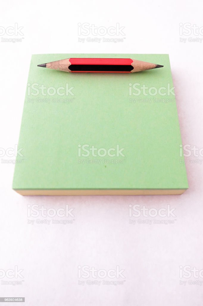 Small red and black pencil, sharpened at both ends, on a green notepad - Royalty-free Adhesive Note Stock Photo