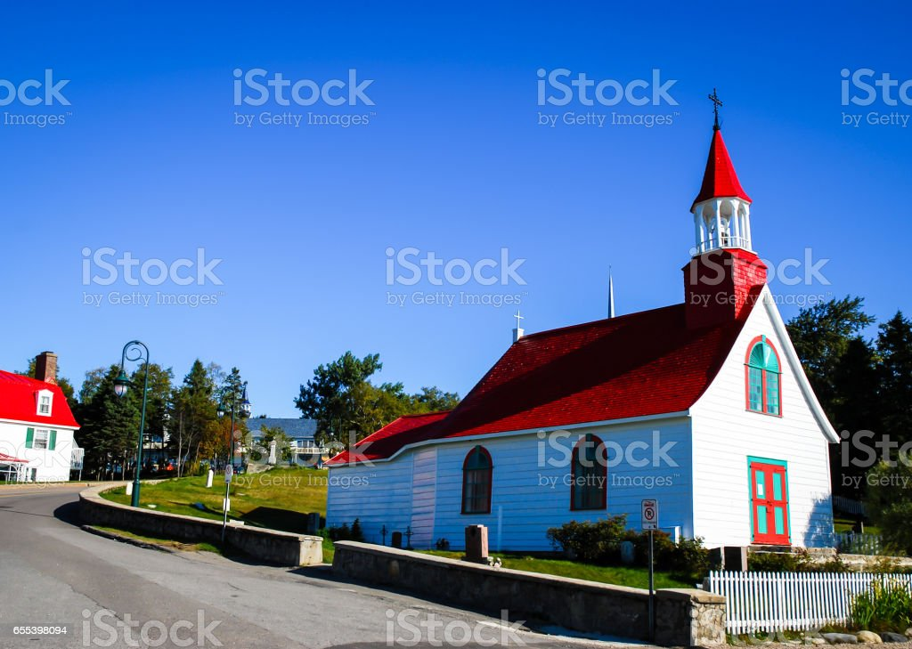 small red and white church in tadoussac canada on a blue sky background stock photo