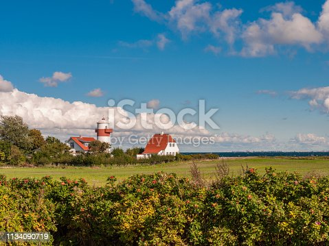 istock Small red and white colored lighthouse with a field in front of a wild blue sky near Lohals on Langeland island, Denmark 1134090719