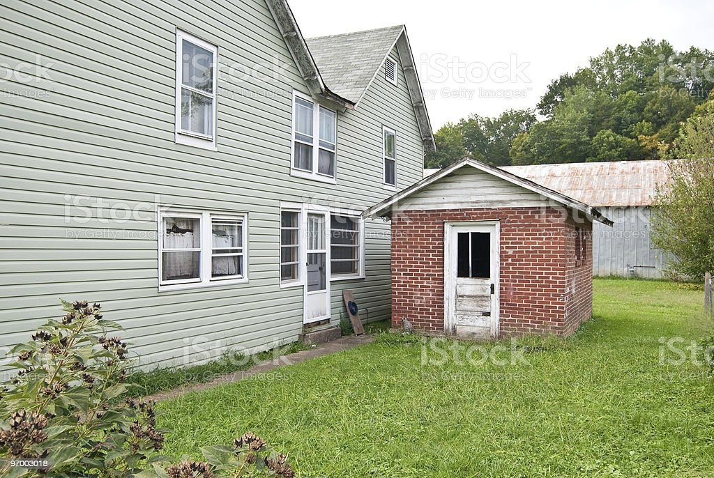 Small Red Brick Building Next to House sitting in Yard stock photo