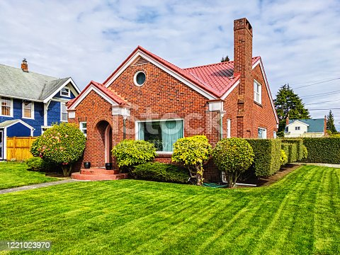 Photo of a small American red brick home on a sunny day