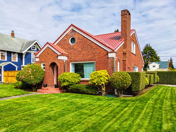 Small Red Brick House with Green Grass stock photo