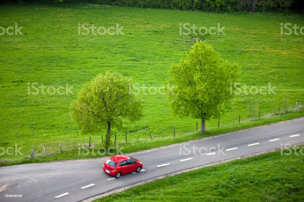 Small Red Car Driving Fast on Country Road stock photo