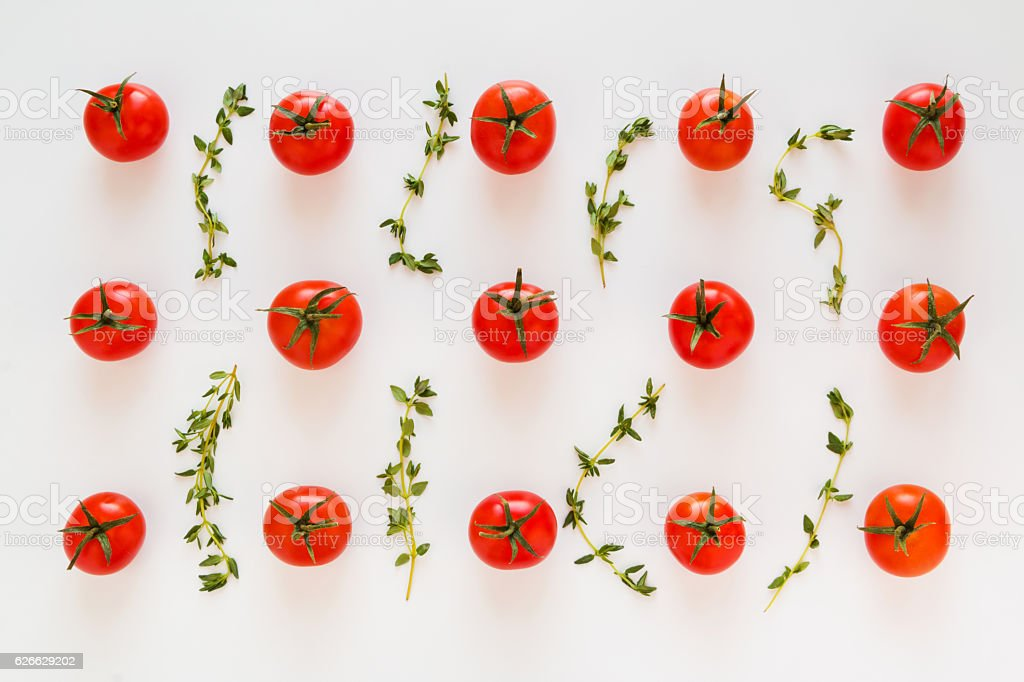 Small red cherry tomatoes and fresh green thyme leaves stock photo