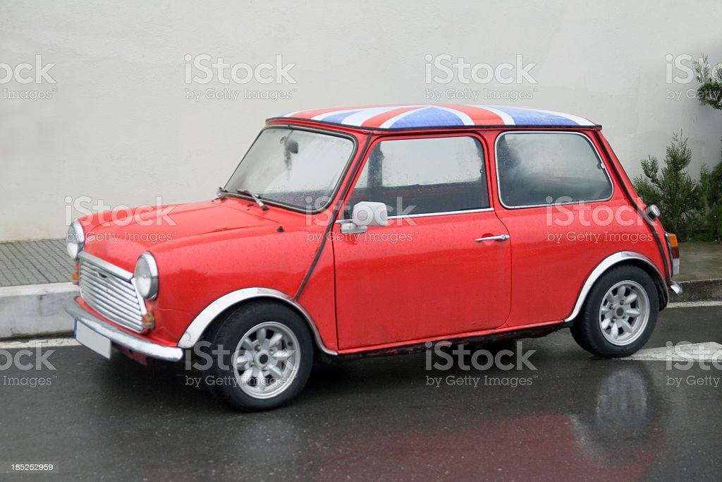 A small, red classic car with an English flag on top stock photo