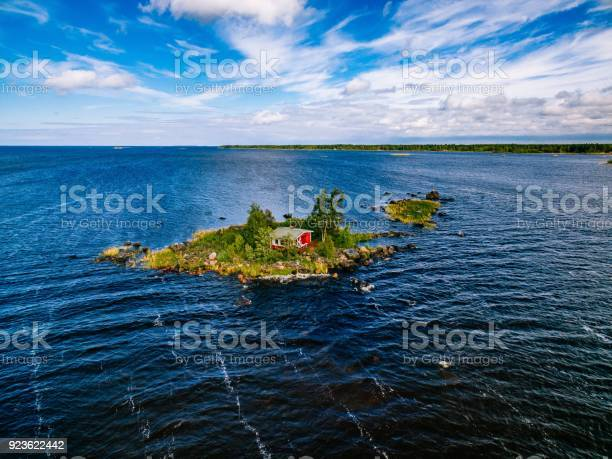 Photo of A small red cottage on an island in the blue sea on a summer day. Finland. View from above.