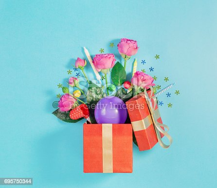 950793576 istock photo Small red gift box with roses, balloon, confetti and candles, top view 695750344