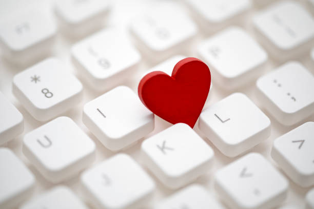 Small red heart on computer keyboard. Internet dating concept. stock photo