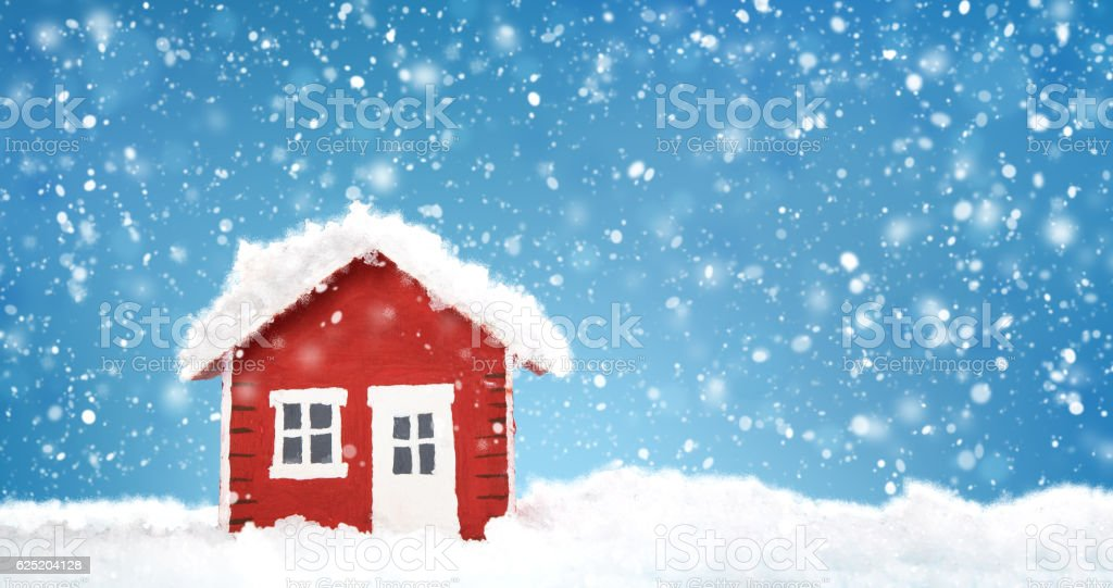 Small red house model covered with snow stock photo