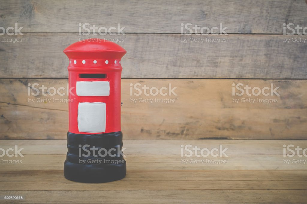 Small red post box on wood background stock photo