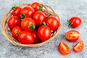 istock Small red ripe tomatoes in wicker wooden bowl 1081839278