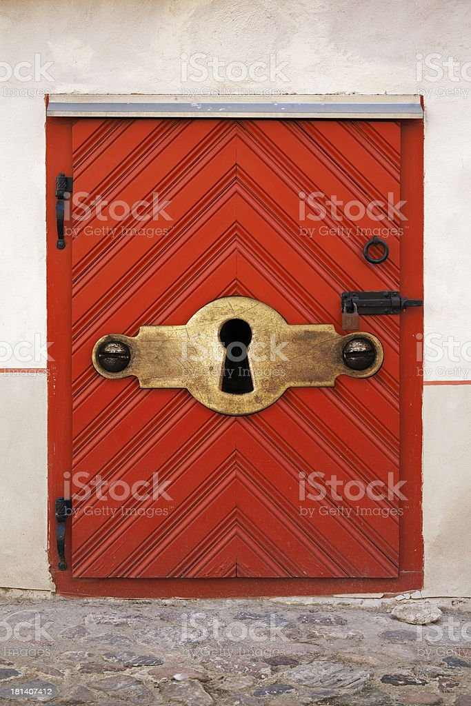 Small Red wooden door with large keyhole royalty-free stock photo