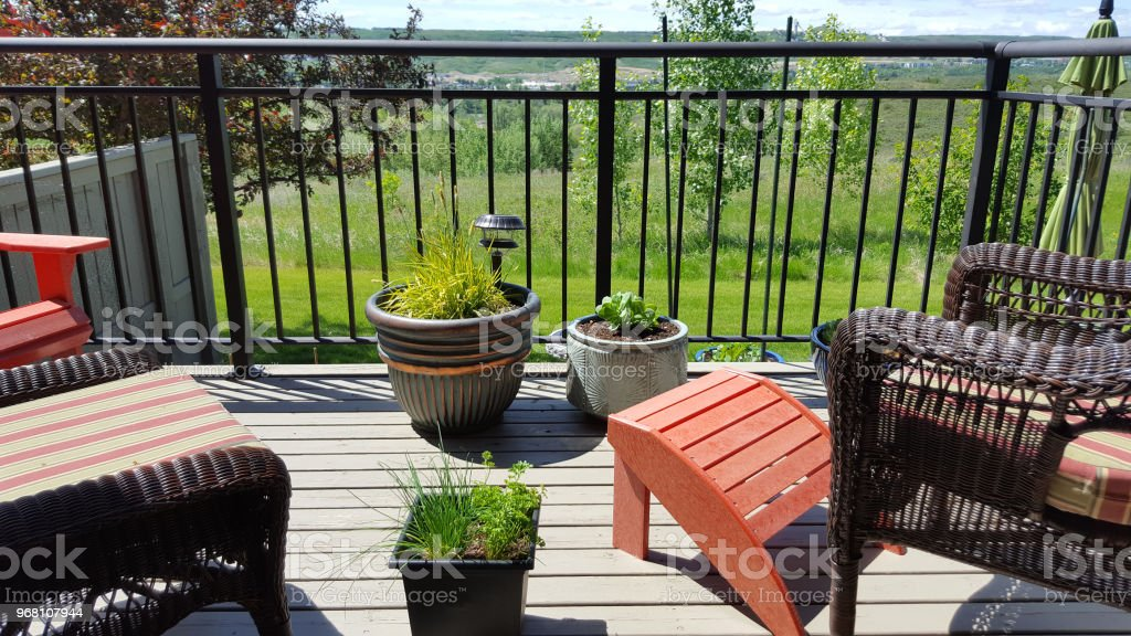 Small Residential Deck with wicker furniture. Growing...
