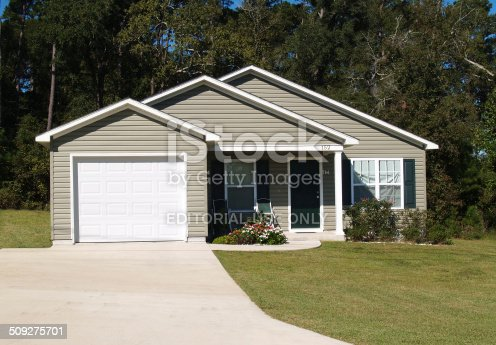 Thomasville, Georgia, October 1, 2009:  A typical low income home in Thomasville, Georgia.  This very small residential home is on a small lot, has a single car front entrance garage,  gray siding with white trim and green door and shutters.