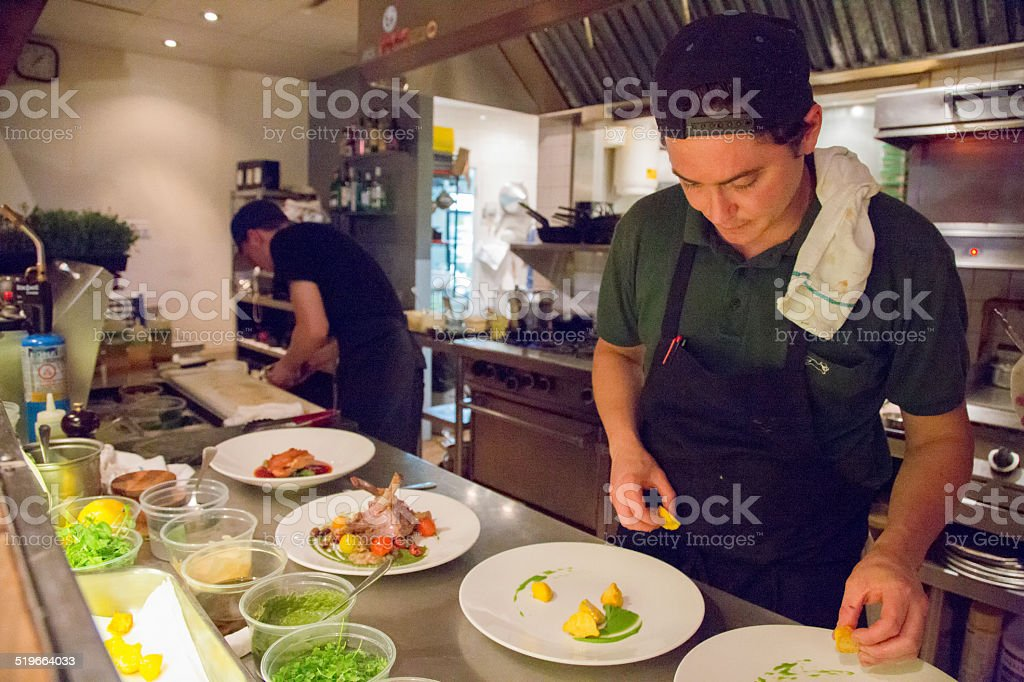 Small restaurant chef plating dishes during evening service stock photo