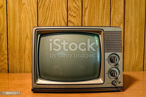 This is a photograph of a small retro television from the 1980s in front of a vintage wood paneled wall.
