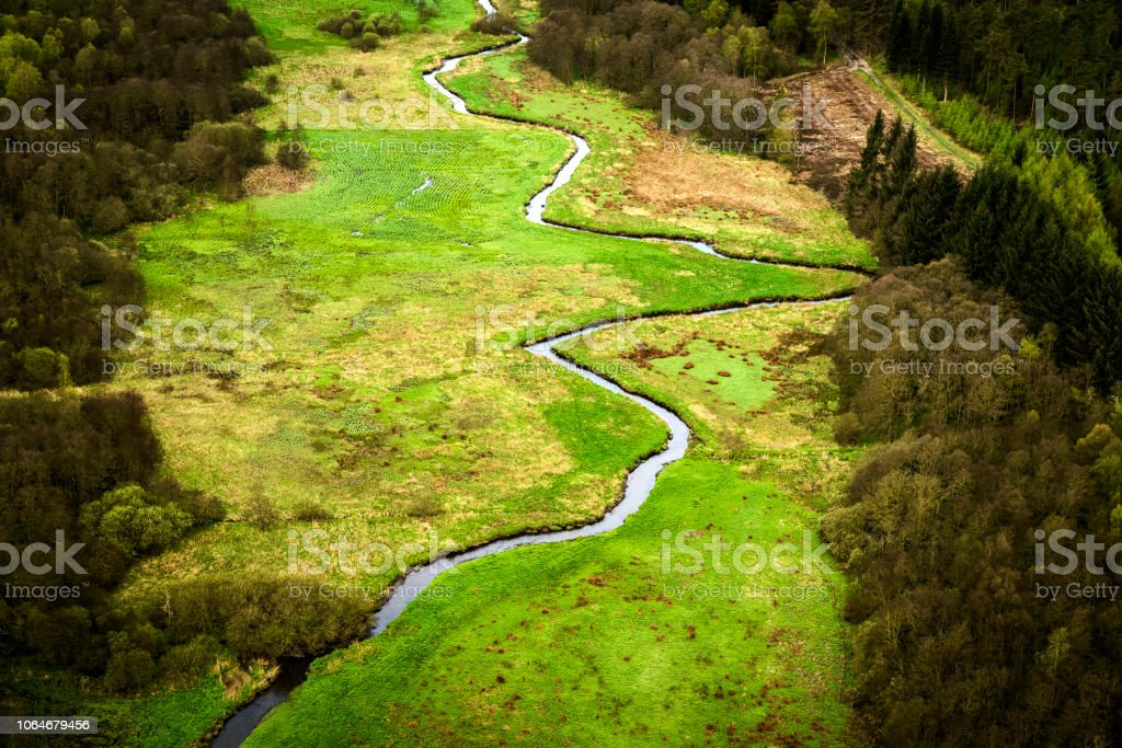 Small river going through a green area with fields stock photo