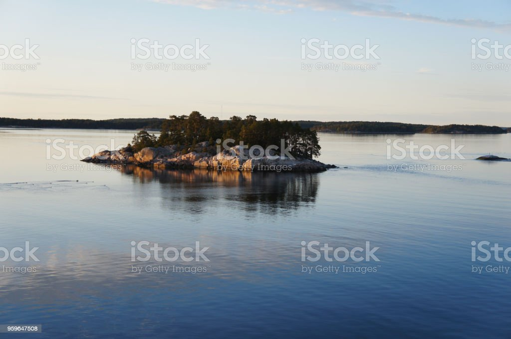 Small rocky island in archipelago of Turku, Finland in sea at sunset stock photo