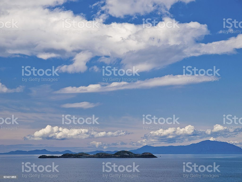 Small rocky island with distant mountains stock photo