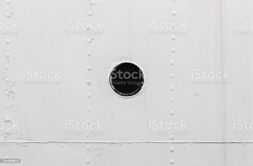 Small round rusted porthole in white ship hull stock photo