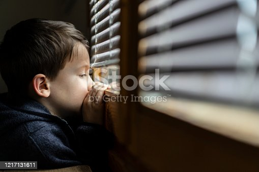 Small sad boy looking through the window. Concept for social distancing during coronavirus pandemic